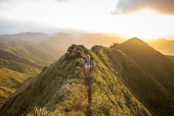 woman walking along path on a mountain ridge
