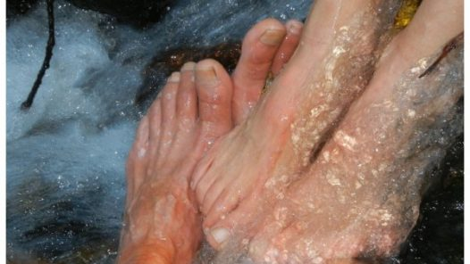 two sets of feet in a waterfall