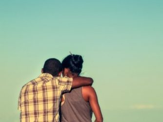 couple with arms around each other sitting on a cliff