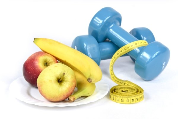 a plate of fruit and a set of dumbbells