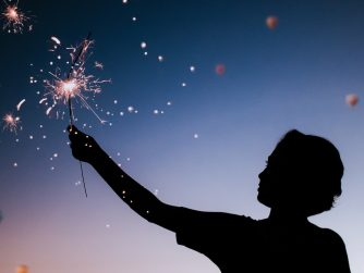 silhouette of boy with sparkler in the night sky