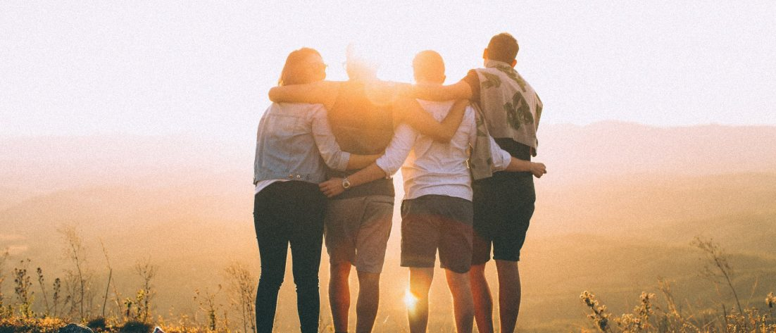 four people standing at sunset