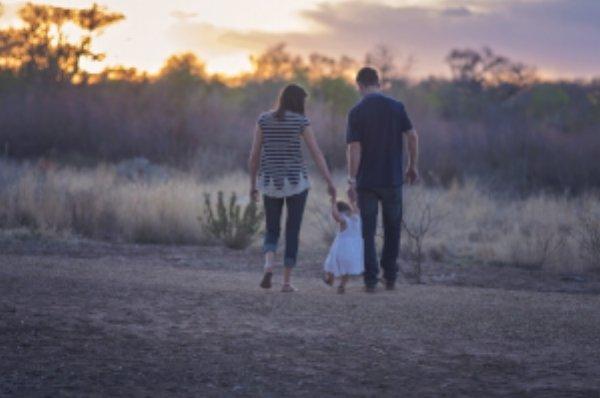 family walking down dirt path at sunset