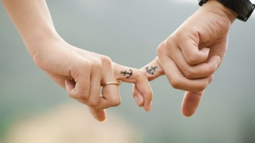 two hands holding fingers with anchor tattoos