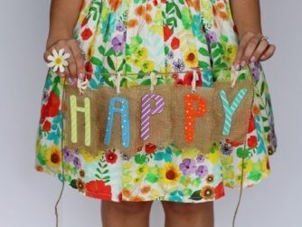 girl holding colorful happy sign