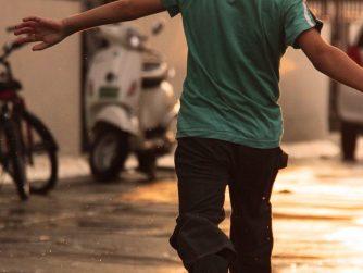 boy in green shirt running down wet street