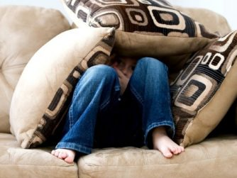 child sitting on couch under pillows