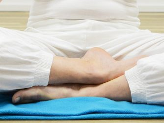 person sitting on blue mat doing meditation