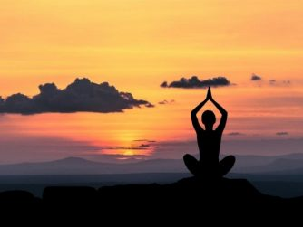 person meditating during sunset