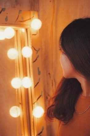 Girl looking at lighted mirror