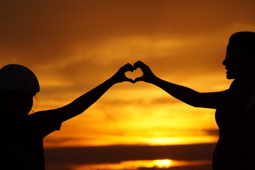 two people forming a heart hand during sunset
