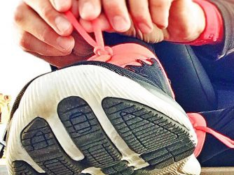 person tying shoes with red laces