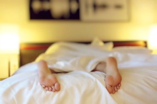 person sleeping in a bed with feet out