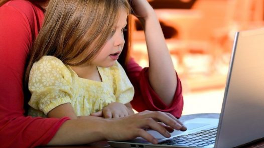child on computer with mother